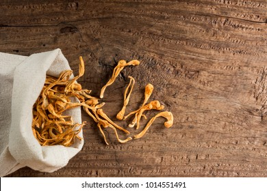 top view of dried cordyceps militaris mushroom with cloth bag on old and crack wooden table. alternative healthy food and medical concept.