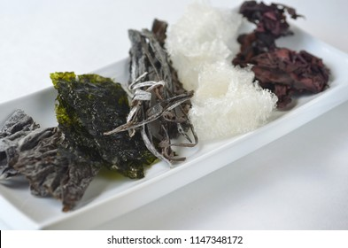Top view of dried edible seaweed varieties - nori, kelp, dulse, wakame, alaria and agar agar