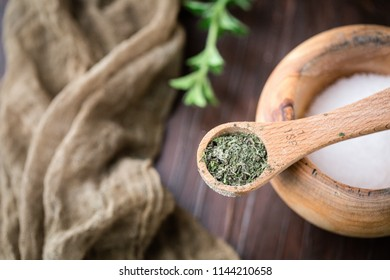 Top View of Dried Oregano Herb in Wooden Teaspoon on Bowl of Salt; Wooden Pestle; Fresh Sprig in Background on Wooden Table Top