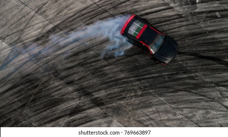 Top view of a drifting car, Aerial view photo from flying drone of drifting car on race track with smoke.
