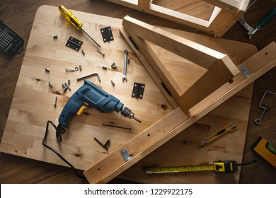 Top view of drill tool and another equipment on wood table furniture.assembly, improvement or repairing home interior concepts ideas