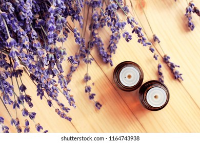 Top view dropper bottles with essential lavender oil. Dried aromatic purple herbal blossom, wooden table.