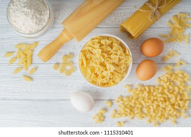 Top view of dry mixed pasta with spaghetti and ingredients for pasta on white wood background.