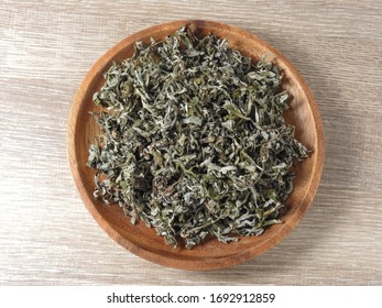 Top view of dry mugwort on wooden plate. Chinese medicine. During the Dragon Boat Festival, is usually hung on the door, which is used to ward off evil spirits and to drive away mosquitoes.