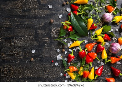 top view of dry and red peppers, sea salt, different greenery on cracks black background