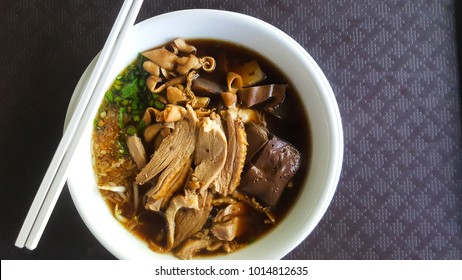 Top view Duck noodle on a white bowl, vice tray and food,One of the menu of Thai noodles that foreigners have to taste, with copy space