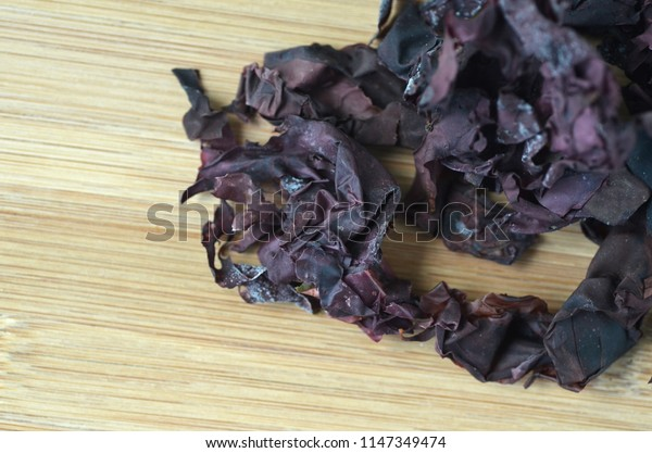 Top view dulse (Palmaria palmata) seaweed on a white plate with copy space.