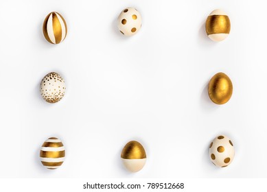 Top view of easter eggs colored with golden paint in differen patterns arranged in square. Various striped and dotted designs. White background. Copy space.