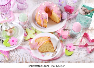 top view of Easter table in pastel colors with partly sliced ring cake with pink icing