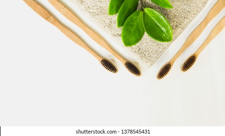 Top view Eco friendly natural bamboo toothbrush,with green leaf natural place on towel a white background, concept reduce use plastic for health and nature Sustainable, with zero waste management