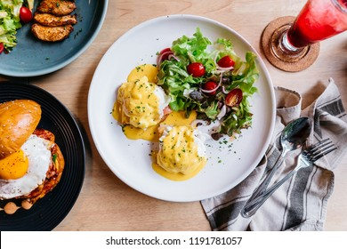 Top view of Egg benedict served with salad in white plate on wooden table for delicious breakfast and brunch.