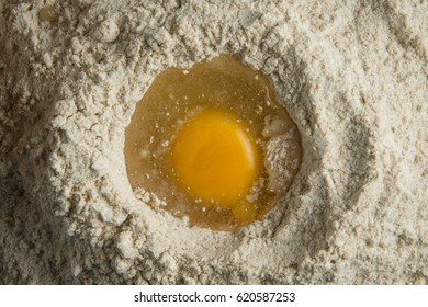 Top view of egg cracked in flour