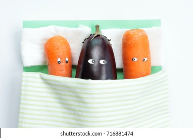 Top view of eggplant lying with two carrots in bed. Above view. Food concept. Sex concept