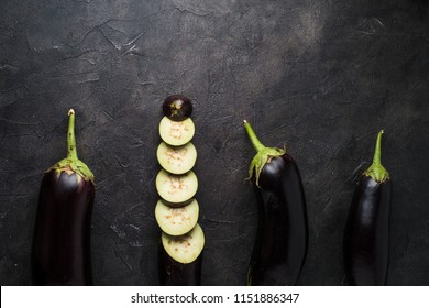 Top view of eggplants on black textured background
