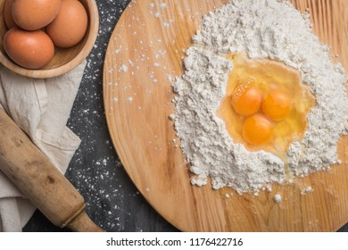Top view eggs, dough, flour and rolling-pin on wooden table background. Preparation for making homemade cake.