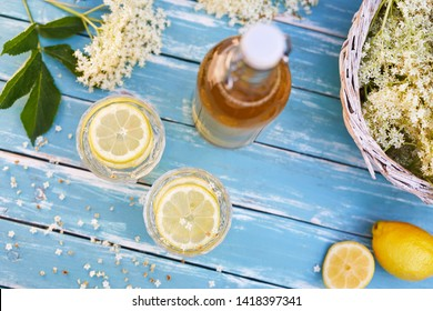 Top view of elderberry lemonade with bottle of syrup and elderberry flowers on wooden table