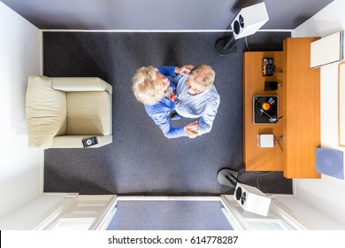 Top view of an elderly couple dancing to some streaming classical music in a small room