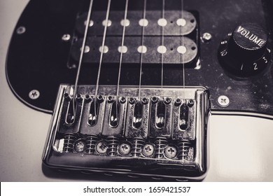 Top view of an electric guitar bridge, pickups and volume control button