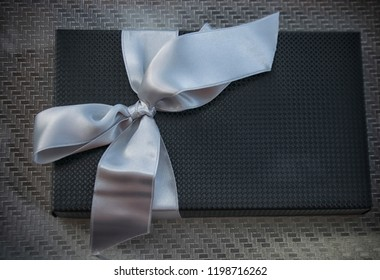 Top view of an elegant black present with a silver bow