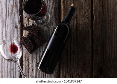 Top view of elegant bottle and wineglasses with red wine and dark chocolate on rustic wooden background. Wine and dessert. Template concept for your design and advertising company promotion.