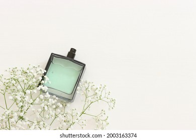 Top view of elegant perfume bottle with flowers over wooden white background. Cosmetics, fragrance and perfumery concept