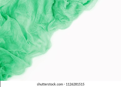 Top view of emerald green colorful gauze fabric isolated on white background with copy space. Flat lay.