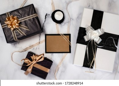 Top view of empty card with gifts ans presents and a little candle. All in black, white and gold colors.
