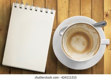 Top view of empty cup of coffee and notepad on top of wooden table