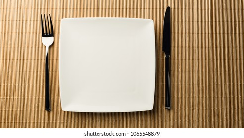 Top view of an empty dining plate with utensils next to it.