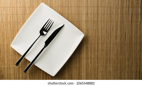 Top view of an empty dining plate with utensils on it.