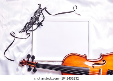 Top view of empty frame, mock up style. Musical wooden instrument strings on white silk textile background. Concept of artistry, music, decoration and creativity, copyspace