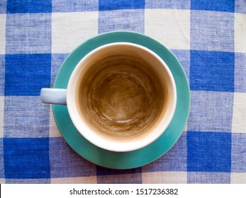 Top view of an empty large cup covered with tea plaque. The dishes are on a blue checkered tablecloth.