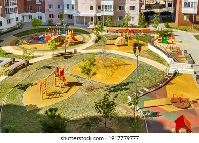 Top view of empty new modern children playground in courtyard of high-rise residential buildings in sunny summer day.