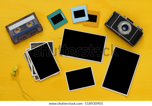 Top view of empty photographs frames next to old camera over yellow wooden table. Flat lay