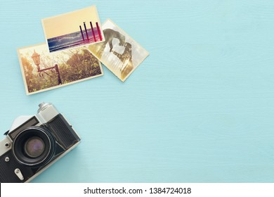 Top view of empty photographs next to camera over wooden table. traveling concept. ready to mock up