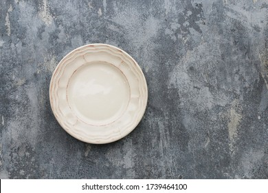 Top view of empty plate on grey, stone background.