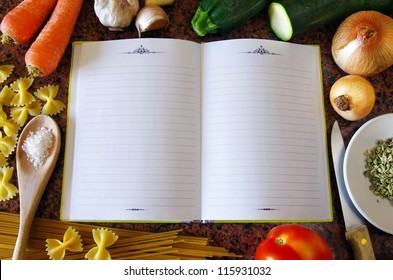 Top view of an empty recipe book surrounded of food ingredients and kitchen utensils