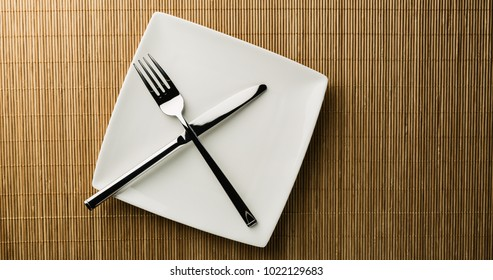 Top view of an empty white dining plate with utensils on it.