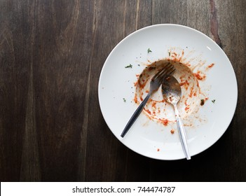 Top view of an empty white plate with some dirty marks of red sauce, green vegetable and pasta with spoon and fork on the plate setting on wooden table with copy space