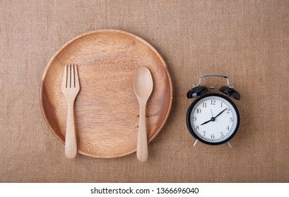 Top view : Empty wood plate with spoon and fork and alarm clock on brown sackcloth. Alarm clock remind eat breakfast. Diet time with empty food on wood plate. proper nutrition, discipline,  adhere to