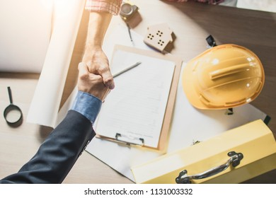 Top view of engineer and businessman shake hands on working table at working site