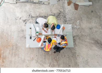 Top view, Engineer group asia and worker meeting, discussion with construction on site work in friendly atmosphere joking and having fun during working process