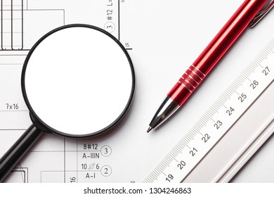 Top view engineering background. Silver ruler, red pen and empty copy space magnifying glass on white paper with project lines.
