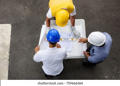 Top view of engineering team of site manager, field engineer and foreman looking at  constructed paper blueprint plans at construction site. Business Concept for team work of heavy industry.