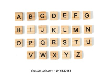 Top view of english alphabet made of square wooden tiles with the English alphabet scattered on a white background with space for text. The concept of thinking development, grammar.