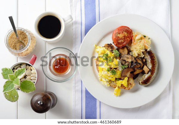 Top view of english breakfast with egg, sausage, vegetable, mushrooms, bread and tomato.