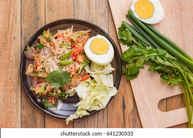 top view enoki mushroom spicy salad. asia thai food on plate at wood background.