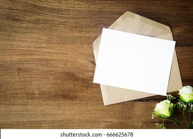 Top view of envelope and blank greeting card with rose flowers on white wooden background.