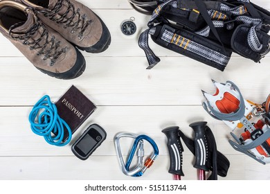 Top view of equipment for hiking on white wood table with empty space in the middle. Items include rope, passport, gps, crampons, carbines, knife, compass, binoculars, trekking pole and shoes.