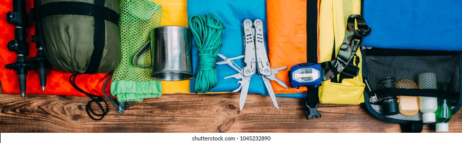 Top view of equipment for hiking and travel on wooden background . Items include trekking pole, multi tool, flashlight, hygiene products, tracking clothes